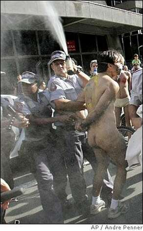 A policeman sprays pepper gas as he detains a man during the World Naked Bike Ride in Sao Paulo, Saturday, June 14 2008. Although the event was authorized, police detained the man for alleged lewd behavior since total nudity is prohibited in public areas in Brazil.