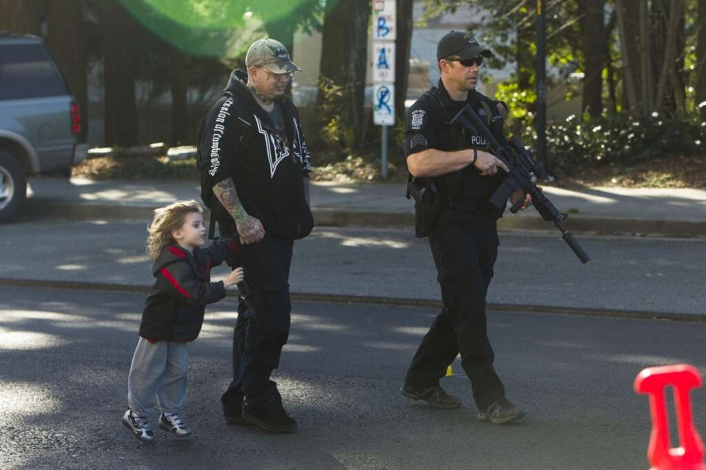 A Seattle SWAT team member escorts Thomas Johnson, center, and his son,  Dameonle