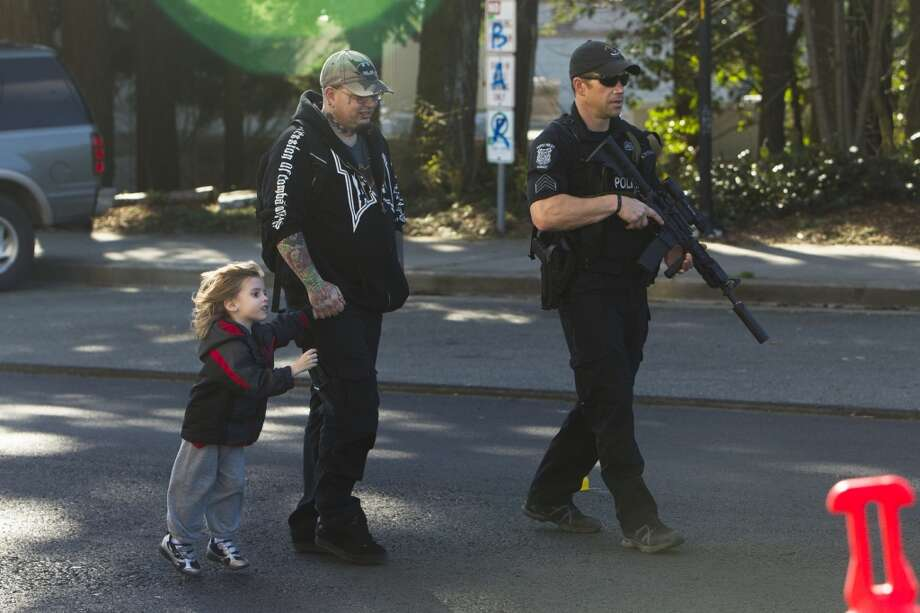 A Seattle SWAT team member escorts Thomas Johnson, center, and his son, Dameonle Gurney, 4, left, away from Bitter Lake Community Center in North Seattle. Johnson had been playing in the park with his son when police approached him, informed him of the situation and escorted him to safety. The suspect in an earlier shooting was seen there waving a gun.