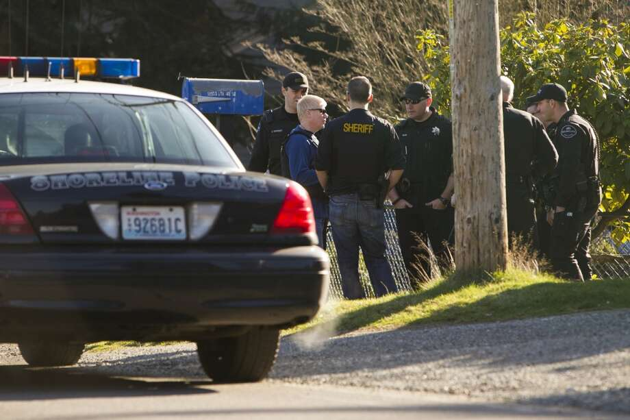 Shoreline Police gather outside of a house following a SWAT raid of the premises in search of a suspect from an earlier shooting in Seattle.