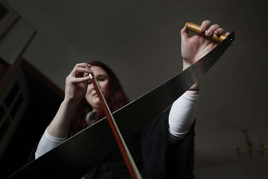 Anika Erdmann practices her musical saw playing in her living room in San Francisco, Calif. Erdmann, who has always wanted to play the saw traded her expertise in social media for the saw. Photo: Mike Kepka, The Chronicle