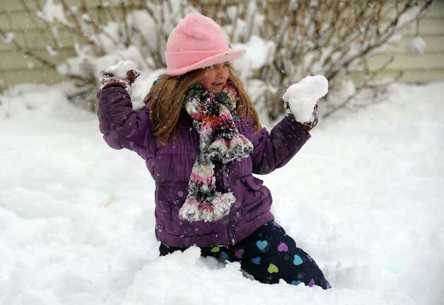 Olivia Leeney, 5, throw snowballs with her brother in their Ansonia backyard Friday, Mar. 8, 2013 as snow falls across the region. Photo: Autumn Driscoll