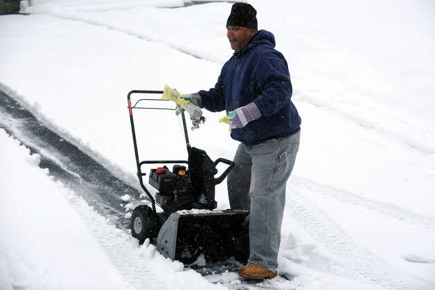 Rodney Spinks digs a mangled newspaper out of the blades of his snow blower, in Stratford, Conn. March 8th, 2013. Photo: Ned Gerard