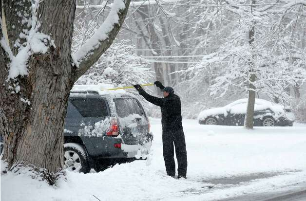 Bill Plotkin cleans off his car on Katona Dr.as snow continues to fall on Friday, March 8, 2013 in Fairfield, Conn. Photo: Cathy Zuraw / Connecticut Post