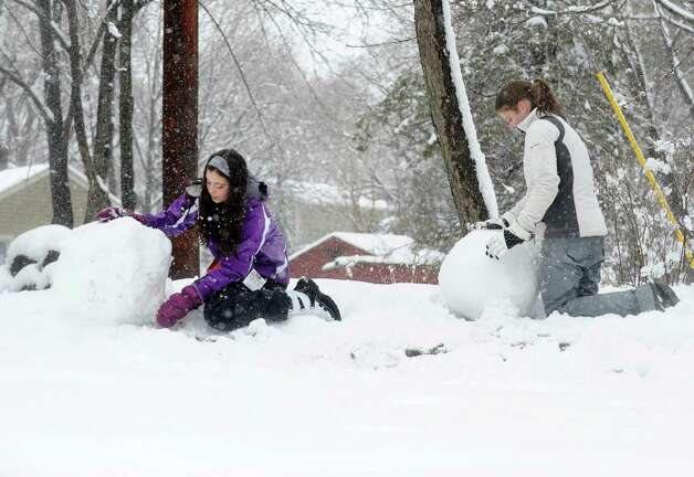 Sisters, Brianna and Hailey Dudding, work on building a snowman in their yard on Buckingham Ave. in Milford, Conn. on Friday March 8, 2013. Photo: Cathy Zuraw / Connecticut Post