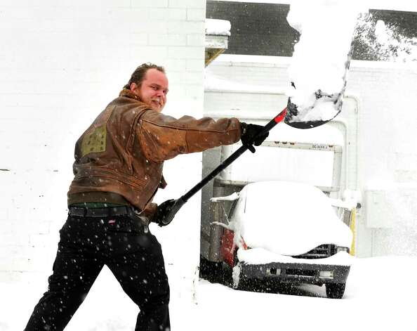 Tom Hibner shovels in front of the U-Haul dealership as Danbury area residents dig out during Friday morning's snow, in Conn. March 8, 2013. Photo: Michael Duffy / The News-Times