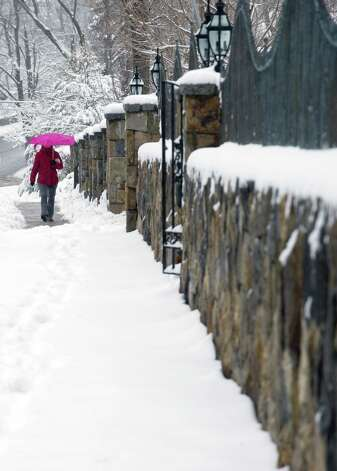 A woman carries an umbrella to shield her from snow as she walks on a sidewalk Stamford on Friday, March 8, 2013. Photo: Lindsay Perry / Stamford Advocate