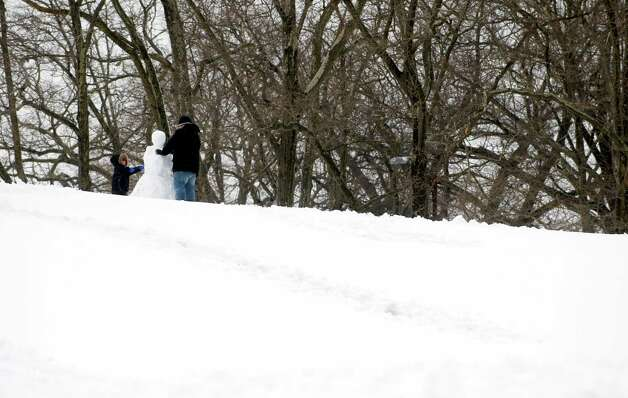 A snowman comes to life on the top of a hill at Cummings Park in Stamford on Friday, March 8, 2013. Photo: Lindsay Perry / Stamford Advocate