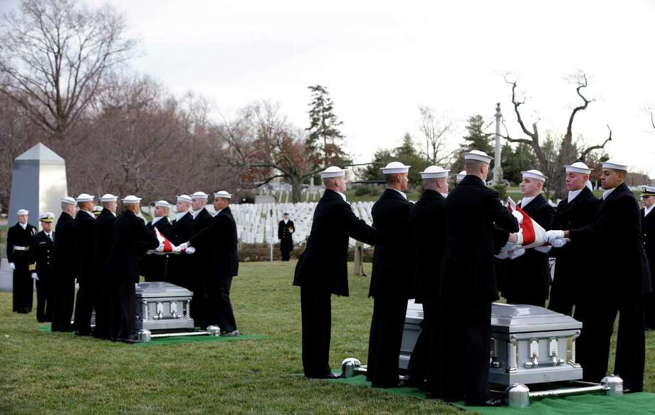 Two honor guard teams simultaneously fold two American flags during services Friday to honor two sailors from the USS Monitor, the Civil War ironclad, held at Arlington National Cemetery in Arlington, Va. Photo: Alex Brandon, STF / AP
