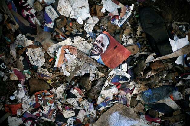 Torn election posters litter the streets of  the Kibera slum of Nairobi, Kenya, Friday, March 8, 2013. Kenyans on Monday held their first presidential vote since the nation's disputed election in 2007 spawned violence that killed more than 1,000 people.  Kenya's last ballots for its presidential race were being counted Friday and Uhuru Kenyatta, the leading candidate, saw his percentage yo-yo above and below the crucial 50 percent mark that would hand him an outright win and avoid a runoff.(AP Photo/Jerome Delay) Photo: Jerome Delay