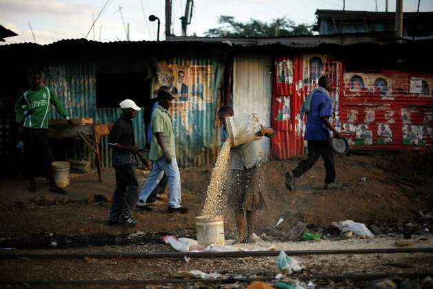 On International Women's day a Kenyan woman transfers corn as men walk by election posters- covered tin walls  in the street of  the Kibera slum of Nairobi, Kenya, Friday, March 8, 2013. Kenyans on Monday held their first presidential vote since the nation's disputed election in 2007 spawned violence that killed more than 1,000 people.  Kenya's last ballots for its presidential race were being counted Friday and Uhuru Kenyatta, the leading candidate, saw his percentage yo-yo above and below the crucial 50 percent mark that would hand him an outright win and avoid a runoff.(AP Photo/Jerome Delay) Photo: Jerome Delay