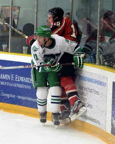 The Whalers' Philip Aucoin puts the Privateers' Sean Walsh into the boards during the FHL playoff semifinal opening game Friday night, Mar. 8, 2013, at the Danbury Arena. Photo: Barry Horn / The News-Times Freelance
