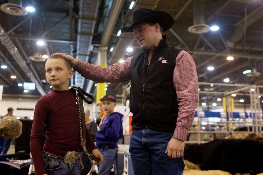 J.D. Sartwelle, 8, waits next to his father, Jim, before J.D. showed Sugie, his Brahman heifer, at  the Houston Livestock Show and Rodeo's Junior Breeding Beef Heifer Show at Reliant Center. Photo: Johnny Hanson, Houston Chronicle / © 2013  Houston Chronicle