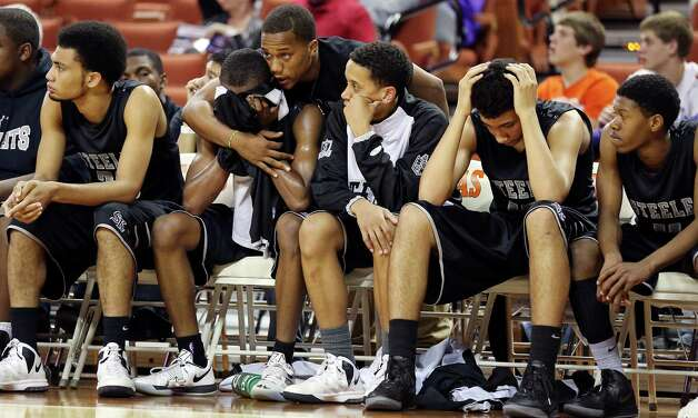 Steele's team manager Jalen Maddox (top center) consoles Steele's C.J. Siples on the bench late in their Class 5A state semifinal game with South Grand Prairie Friday March 8, 2013 at the Frank Erwin Center in Austin, Tx. South Grand Prairie won 60-43. Photo: Edward A. Ornelas, Edward A. Ornelas / San Antonio Express-News / © 2013 San Antonio Express-News