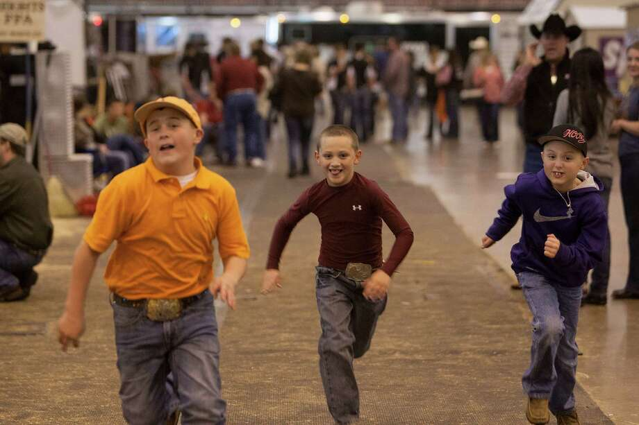 J.D. Sartwelle, 8, center, races with friends Payton Herzog, 12, left, and Collin Parker, 9, before J.D. showed Sugie, at the Houston Livestock Show and Rodeo's Junior Breeding Beef Heifer Show at Reliant Center Friday, March 8, 2013, in Houston. Photo: Johnny Hanson, Houston Chronicle / © 2013  Houston Chronicle