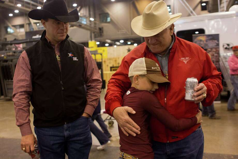 "J.D. Sartwelle, 8, gives his grandfather Jim ""Bubba"" Sartwelle a hug next to his father, Jim, before J.D. showed Sugie, his Brahman heifer at  the Houston Livestock Show and Rodeo's Junior Breeding Beef Heifer Show at Reliant Center Friday, March 8, 2013, in Houston. Photo: Johnny Hanson, Houston Chronicle / © 2013  Houston Chronicle"