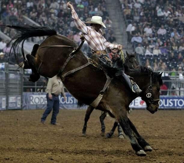 Rhys Angland competes during the Saddle Bronc Riding competition at RodeoHouston in Reliant Stadium