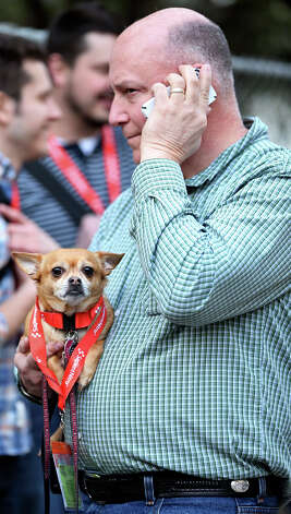 "DoGood Designs' Dave Brackmann and his dog ""Amigo"" wait in line to enter the registrants lounge at Brush Square Park during South by Southwest Friday March 8, 2013 in Austin, TX. Photo: Edward A. Ornelas, San Antonio Express-News / © 2013 San Antonio Express-News"