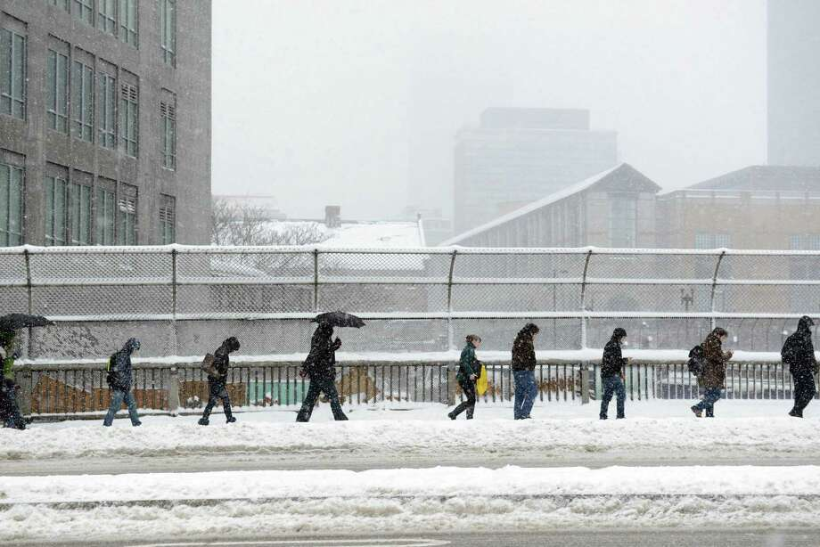 People walk along Boston's Massachusetts Avenue during a storm that left as much as a foot or two of snow in some areas. Photo: Darren McCollester / Getty Images