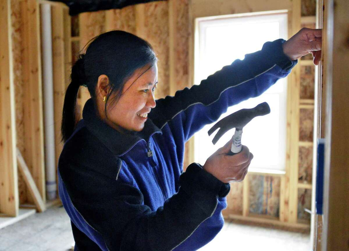 Burmese refugee Steah Htoo from Myanmar hammers a nail at her new Habitat for Humanity house in Albany on Thursday, March 7, 2013. (John Carl D'Annibale / Times Union)