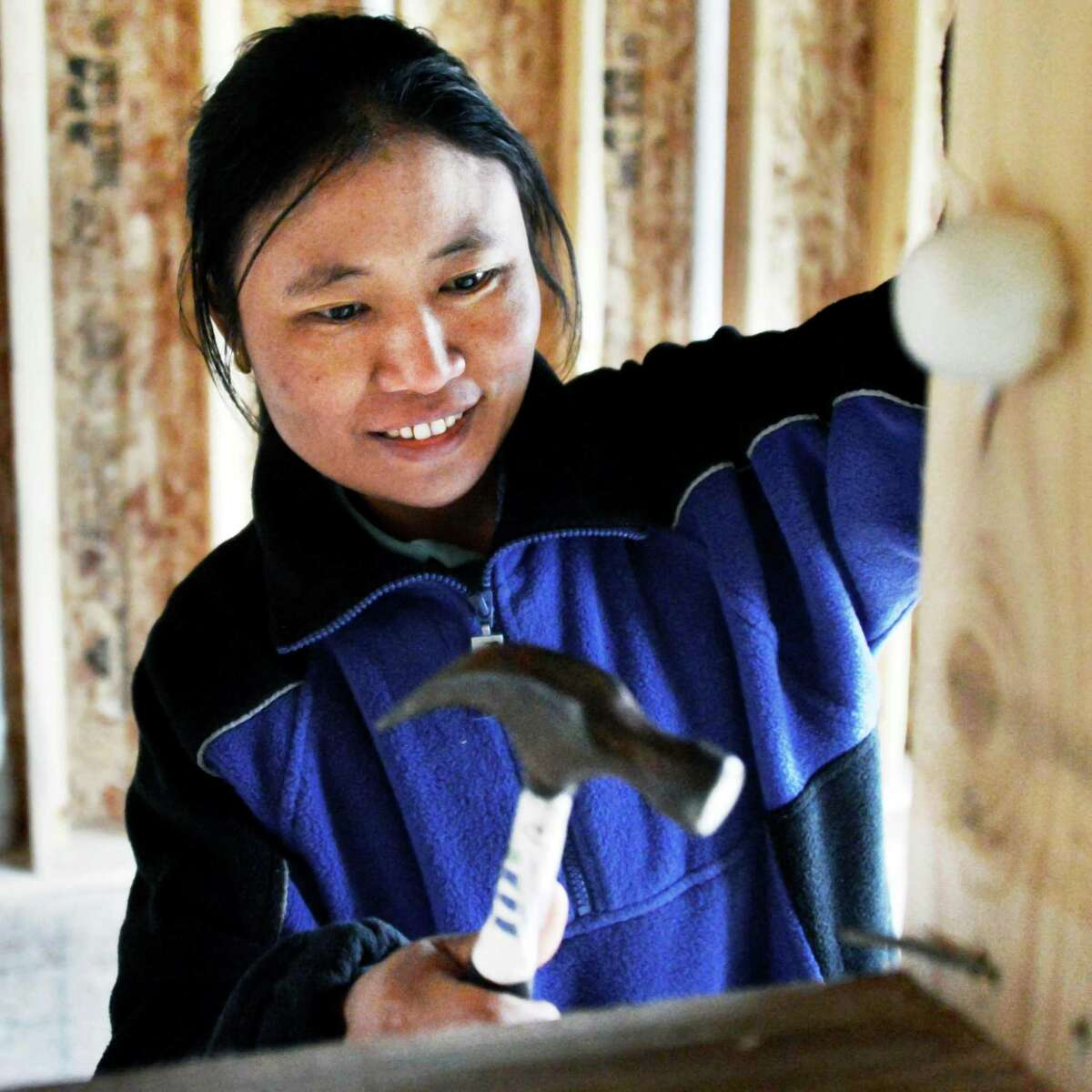 Steah Htoo from Myanmar hammers a nail at her new Habitat for Humanity house in Albany on Thursday, March 7, 2013. (John Carl D'Annibale / Times Union)