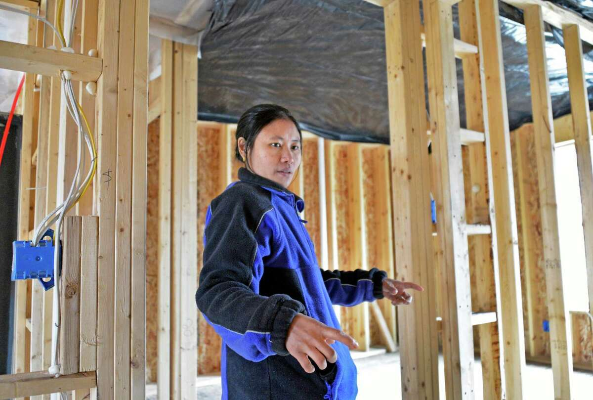 Steah Htoo from Myanmar describes the floor plan at her new Habitat for Humanity house in Albany on Thursday, March 7, 2013. (John Carl D'Annibale / Times Union)