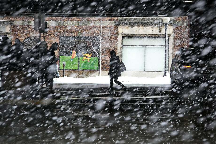 A woman makes her way across the bus station in downtown New Bedford, Mass., as heavy snow falls Friday, March 8, 2013. The storm dropped up to a foot of snow in some parts of New England, caused coastal flooding in Massachusetts. (AP Photo/The Standard-Times, Peter Pereira) Photo: Peter Pereira, Associated Press
