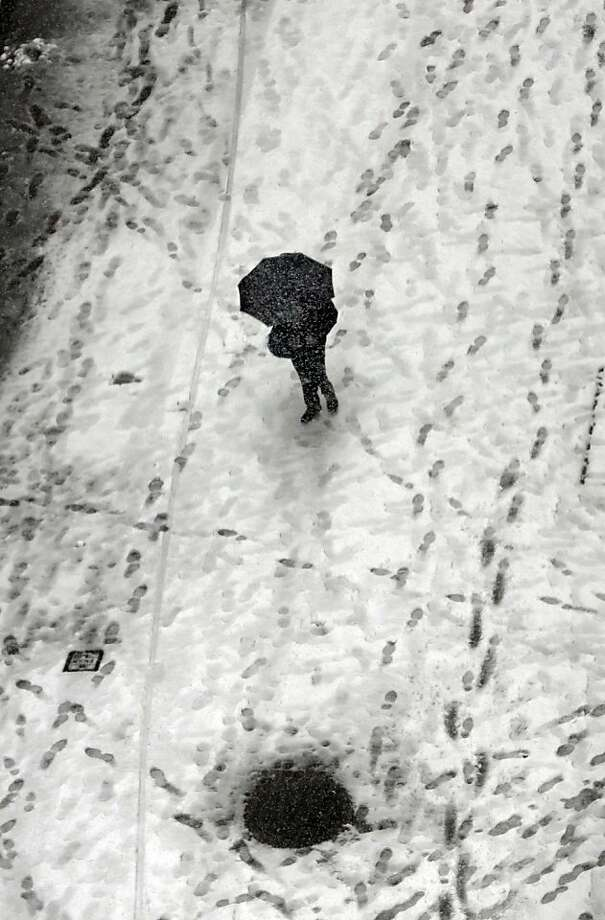 A person walks along snow-covered Wall Street in New York Friday, March 8, 2013. A very wet snow is causing slippery road conditions in the New York metropolitan area. Snow flurries are expected to continue until about noon Friday before changing to rain. (AP Photo/Richard Drew) Photo: Richard Drew, Associated Press