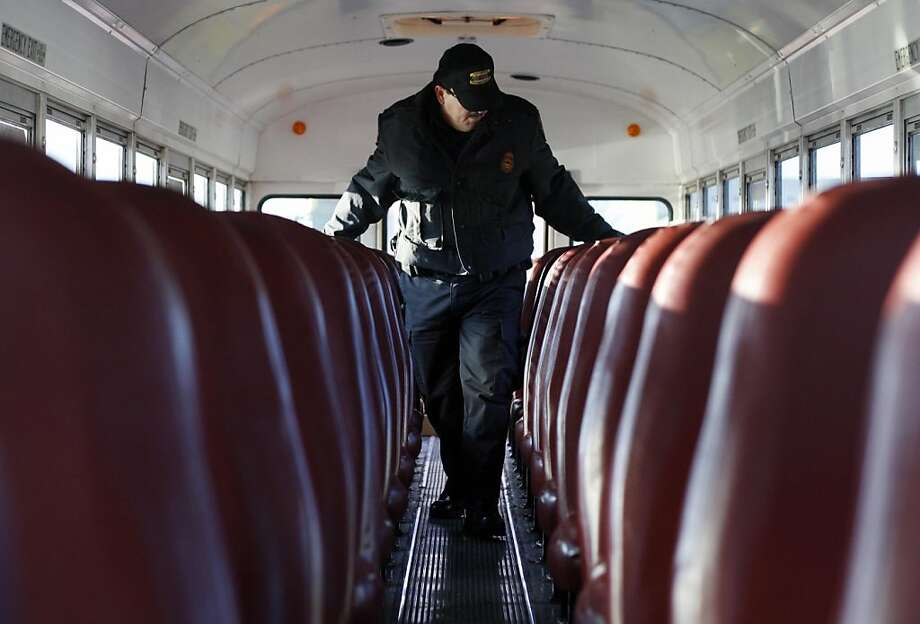 In this photo taken Friday, March 8, 2013, Tennessee State Trooper Wade Clepper checks seats on a Hamilton County school bus during a surprise inspection at Soddy-Daisy High School in Soddy-Daisy, Tenn.  Troopers conduct periodic surprise inspections on school buses in addition to annual scheduled inspections to help insure compliance with safety and mechanical standards. (AP Photo/Chattanooga Times Free Press, Doug Strickland) THE DAILY CITIZEN OUT; NOOGA.COM OUT; CLEVELAND DAILY BANNER OUT; LOCAL INTERNET OUT; MANDATORY CREDIT: DOUG STRICKLAND/CHATTANOOGA TIMES FREE PRESS Photo: Doug Strickland, Associated Press