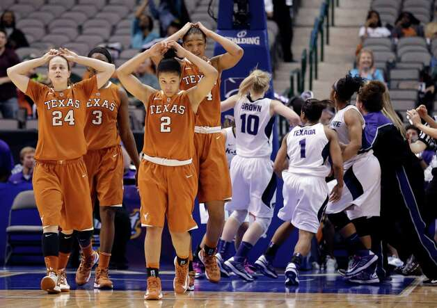 Texas' Chassidy Fussell (24), Nneka Enemkpali (3), Celina Rodrigo (2) and Imani McGee-Stafford (34) walk off as Kansas State celebrates following an NCAA college basketball game in the Big 12 women's tournament Friday, March 8, 2013, in Dallas. Kansas State won 51-49. (AP Photo/Tony Gutierrez) Photo: Tony Gutierrez, Associated Press / AP