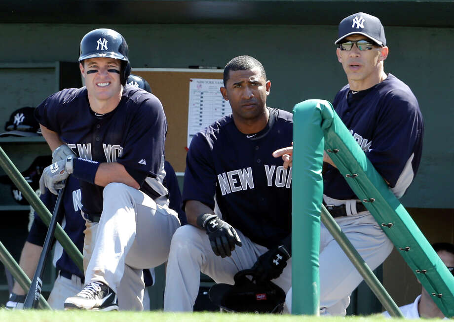 New York Yankees manager Joe Girardi, right, watches from the dugout along side Eduardo Nunez, center, and Jayson Nix during the second inning of an exhibition spring training baseball game against the Miami Marlins Friday, March 8, 2013, in Jupiter, Fla. The Marlins won 6-1. (AP Photo/Jeff Roberson) Photo: Jeff Roberson