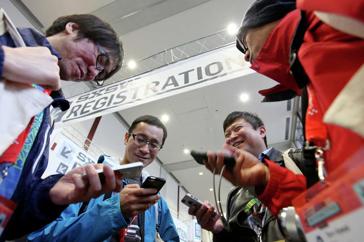 Yahoo Japan employees Kazuhiro Ninomiya, left, Takamitsu Iriyama, Toshiaki Chiku and Taro Kawai work on their smartphones at the SXSW Interactive Festival in Austin.