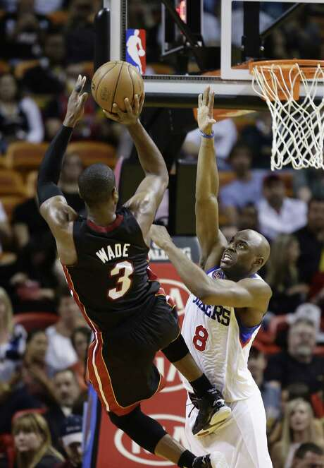 The 76ers' Damien Wilkins reaches to try and block Miami's Dwyane Wade, who scored 22 points in the Heat's 102-93 victory. Photo: J. Pat Carter / Associated Press