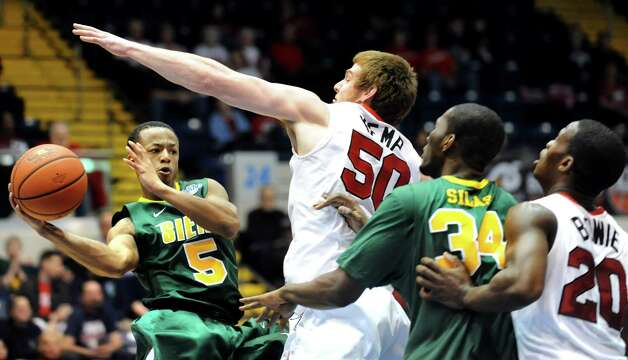 Siena's Evan Hymes (5), left, looks to pass beyond the reach of Marist's Adam Kemp (50), center, during their first round MAAC Championship basketball game on Friday, March 8, 2013, at MassMutual Center in Springfield, Mass. (Cindy Schultz / Times Union) Photo: Cindy Schultz / 10021490A