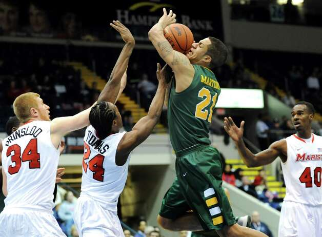 Siena's Davis Martens (21), center, goes to the hoop and draws a foul from Marist's Manny Thomas (24), second from left, during their first round MAAC Championship basketball game on Friday, March 8, 2013, at MassMutual Center in Springfield, Mass. (Cindy Schultz / Times Union) Photo: Cindy Schultz / 10021490A