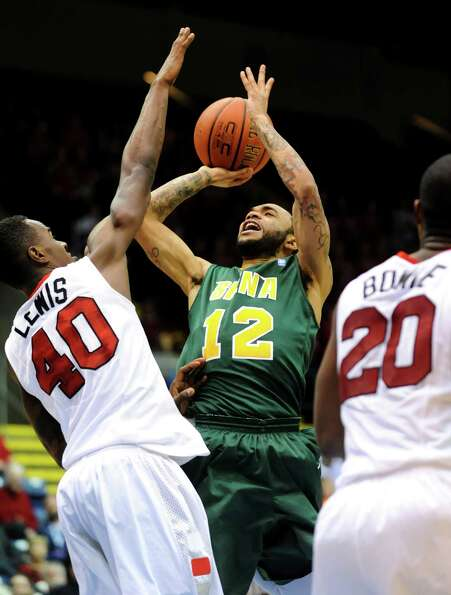 Siena's Rakeem Brookins (12), center, shoots and draws a foul from Marist's Chavaughn Lewis (40), le