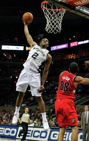 Kawhi Leonard soars for a slam as Nicolas Batum stands back as the Spurs play the Portland Trail Blazers at the AT&T Center on March 8, 2013. Photo: TOM REEL