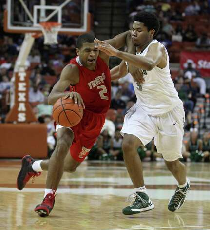 Travis' Aaron Harrison (2) struggles to get past Richardson Berkner's Tory Everett (3) in the second half of Friday night's Class 5A semifinal at Austin. Harrison led the Tigers with 19 points and eight rebounds as they won 60-52 to advance to the title game for the second consecutive year. Photo: Karen Warren, Staff / © 2013 Houston Chronicle