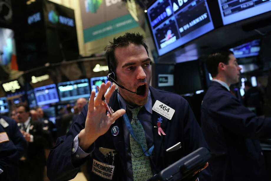 The Dow Jones industrial average has gained 9.9 percent this year and was at record levels last week, keeping this trader busy. Photo: Spencer Platt, Staff / 2013 Getty Images
