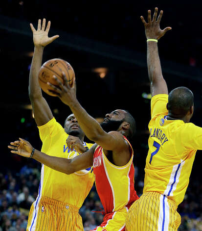Rockets shooting guard James Harden shoots between Festus Ezeli and Carl Landry of the Warriors. Photo: Ben Margot
