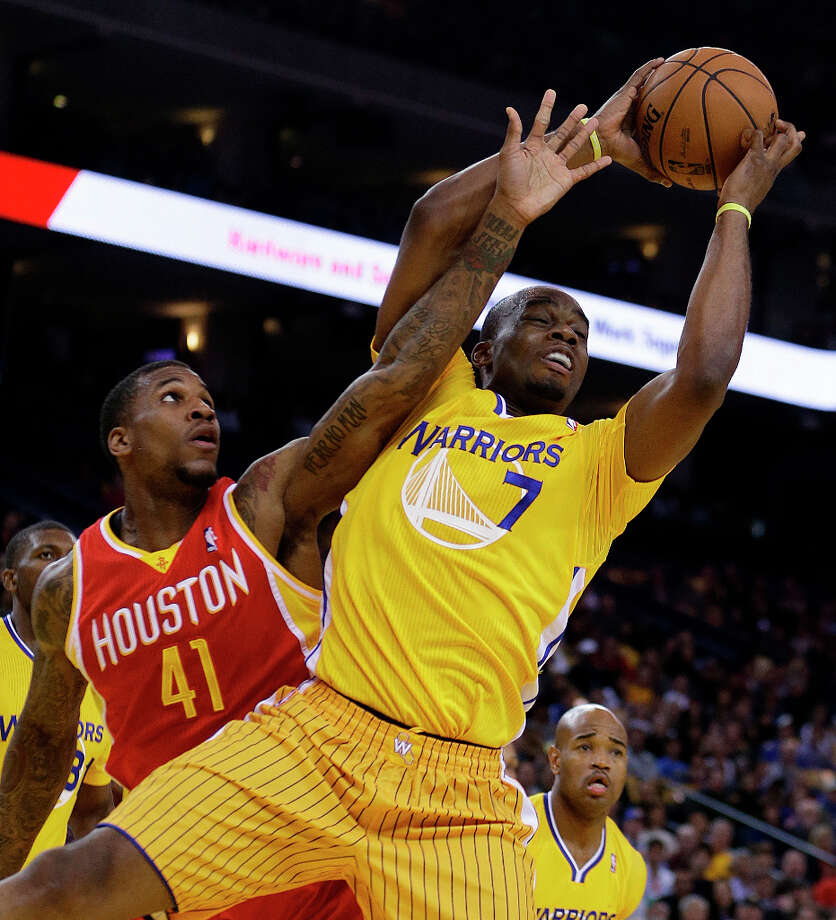 Rockets forward Thomas Robinson defends Carl Landry of the Warriors. Photo: Ben Margot