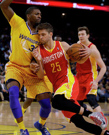 Rockets forward Chandler Parsons drives against Festus Ezeli of the Warriors. Photo: Ben Margot