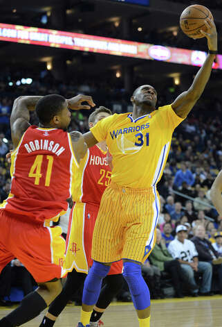 Festus Ezeli of the Warriors grabs a rebound against Thomas Robinson of the Rockets. Photo: Dan Honda