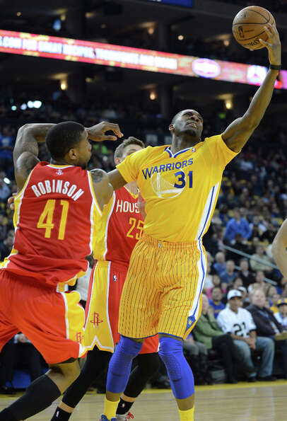 Festus Ezeli of the Warriors grabs a rebound against Thomas Robinson of the Rockets.