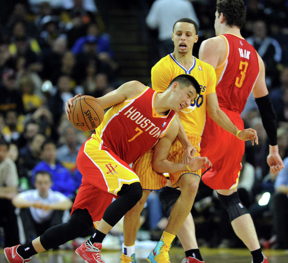 Warriors guard Stephen Curry tries to fight through a screen by Rockets center Omer Asik as guard Jeremy Lin drives. Photo: Dan Honda