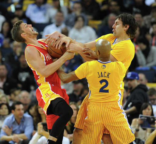 Andrew Bogut and Jarrett Jack of the Warriors battle for possession with Rockets forward Chandler Parsons. Photo: Dan Honda