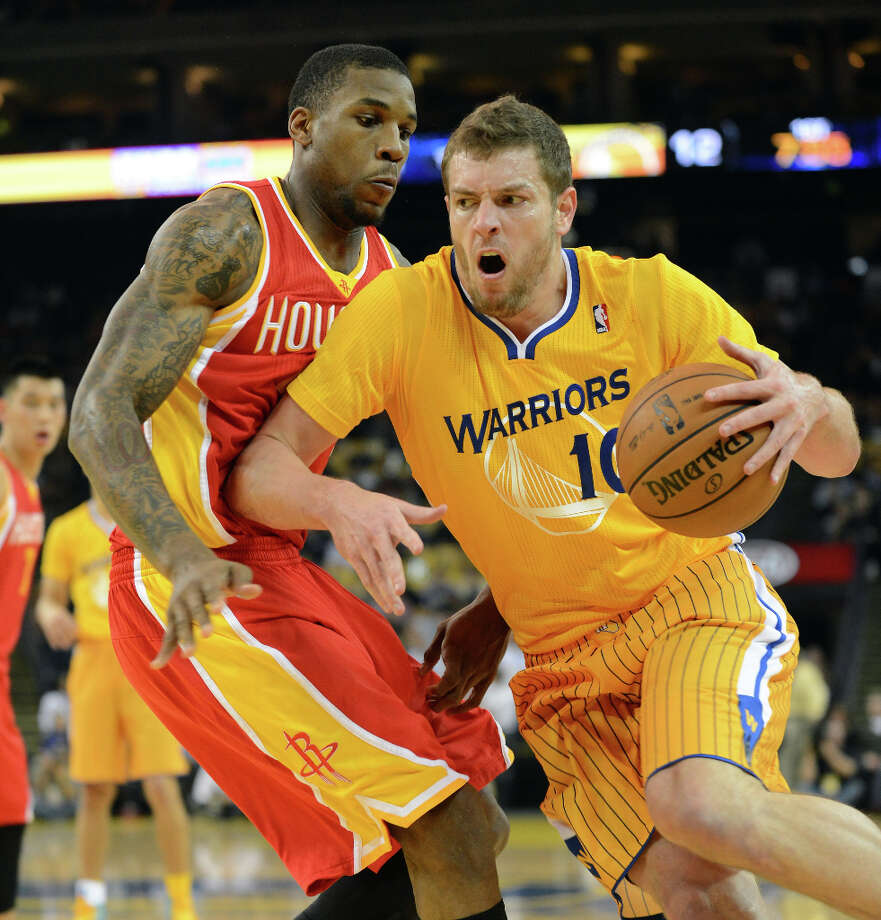 Warriors forward David Lee drives against Thomas Robinson of the Rockets. Photo: Dan Honda