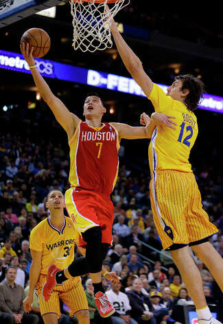 Rockets guard Jeremy Lin lays up a shot against Andrew Bogut of the Warriors. Photo: Ben Margot