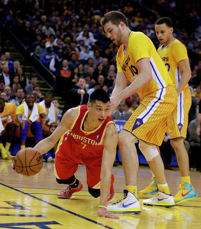 Rockets point guard Jeremy Lin tries to pass the ball while facing pressure from David Lee of the Warriors. Photo: Ben Margot