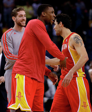 Rockets players Thomas Robinson, Chandler Parsons and Carlos Delfino celebrate after beating the Warriors. Photo: Ben Margot